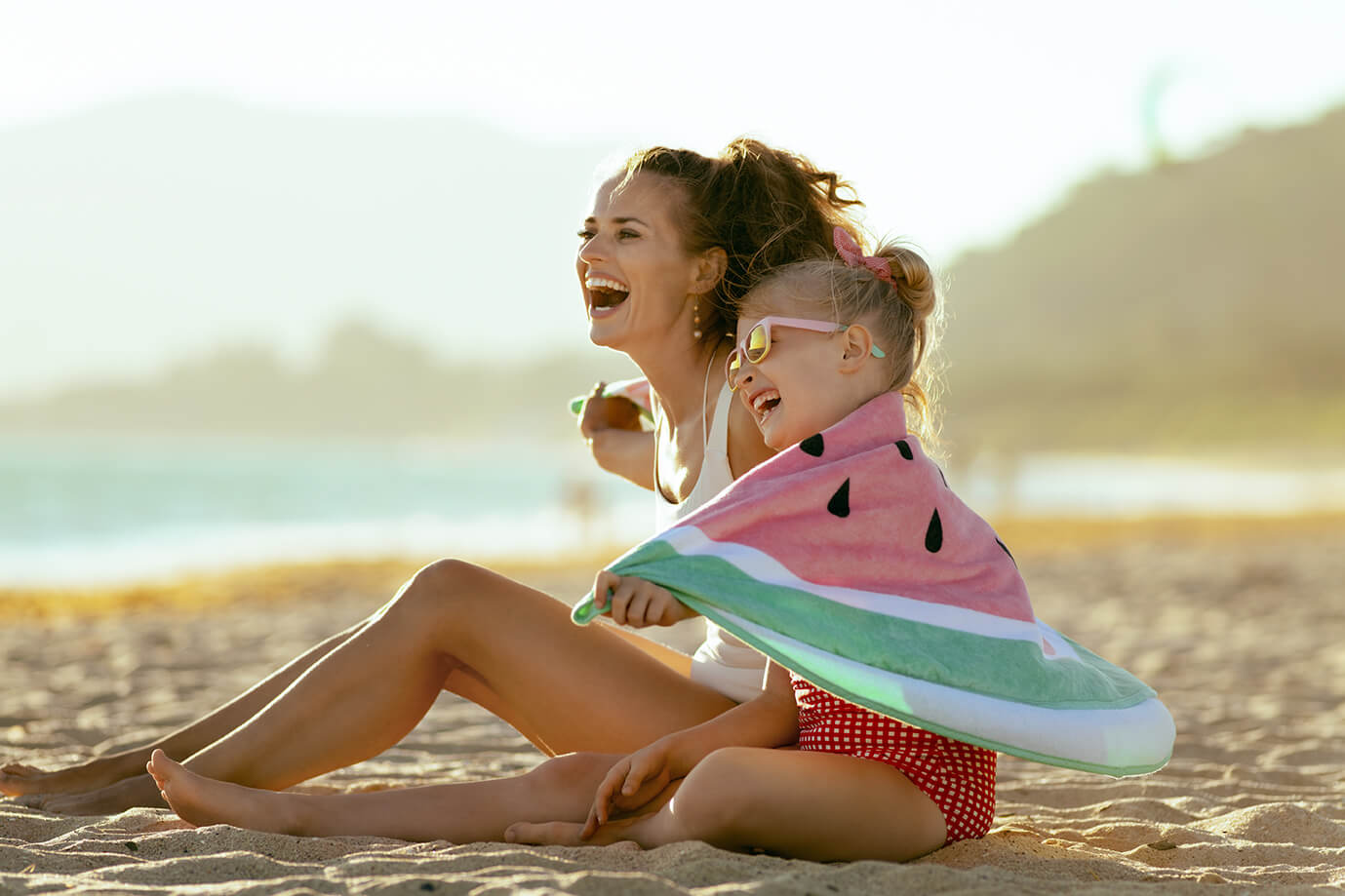 Mother and daughter on the beach before swimming with lash extensions