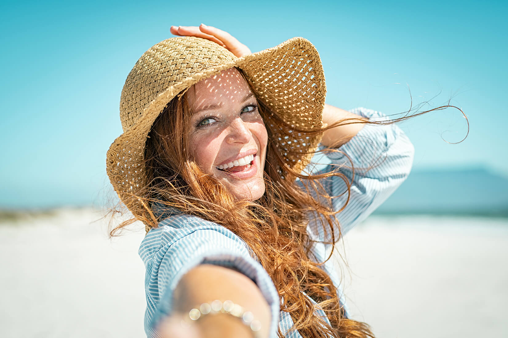 Woman on beach thinking about swimming with eyelash extensions
