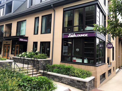 Exterior shot of The Lash Lounge salon with lush green landscape