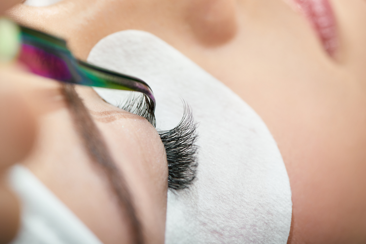 woman lying down with eyes closed while she is getting her volume eyelash extensions refilled at a lash salon
