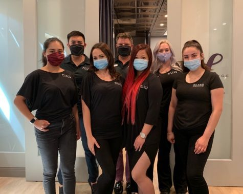 the happy staff and owner from The Lash Lounge Chicago River North standing together as a team inside the salon wearing masks