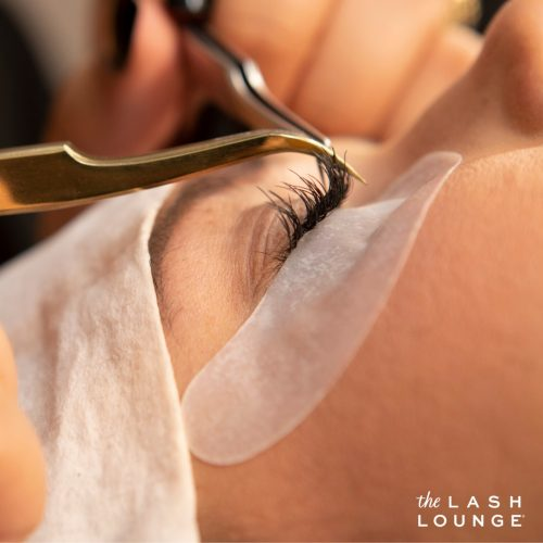 side closeup view of one closed eye of woman during a lash extension application with tweezers applying the lash extension to her natural eyelash