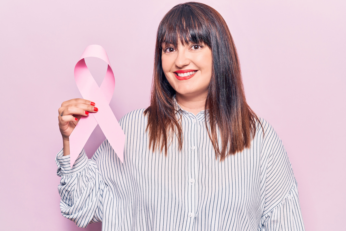 brunette woman standing infant of a pink background smiling and holding a pink ribbon for breast cancer awareness