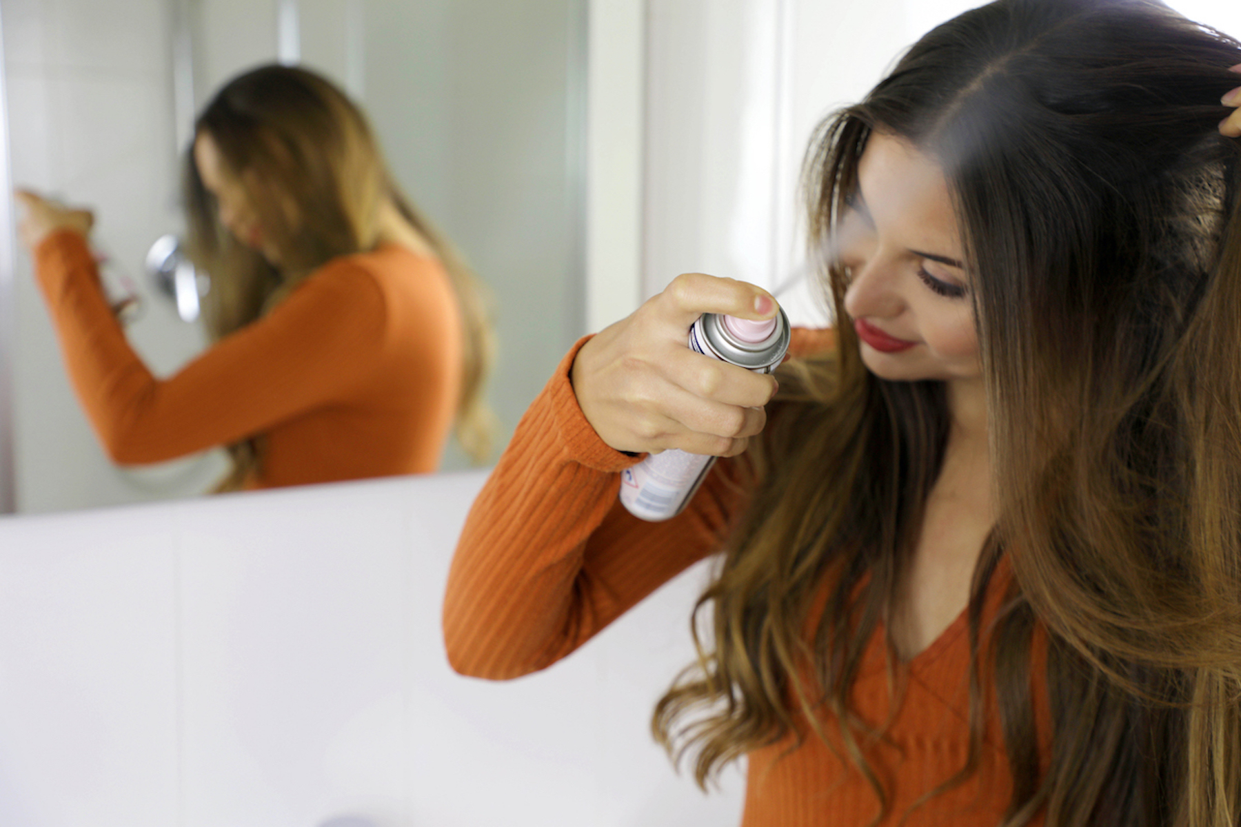brunette woman with eyelash extensions spraying her hair with hairspray