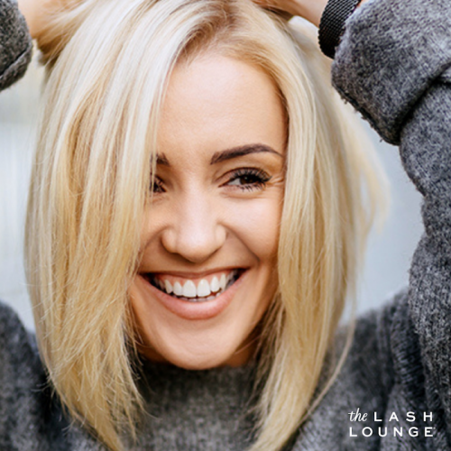 happy smiling blonde woman wearing a sweater with her freshly tinted and threaded eyebrows