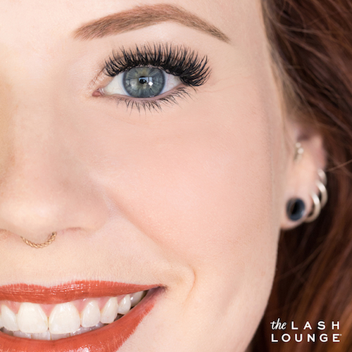 smiling redheaded woman wearing red lipstick with threaded eyebrows and lash extensions