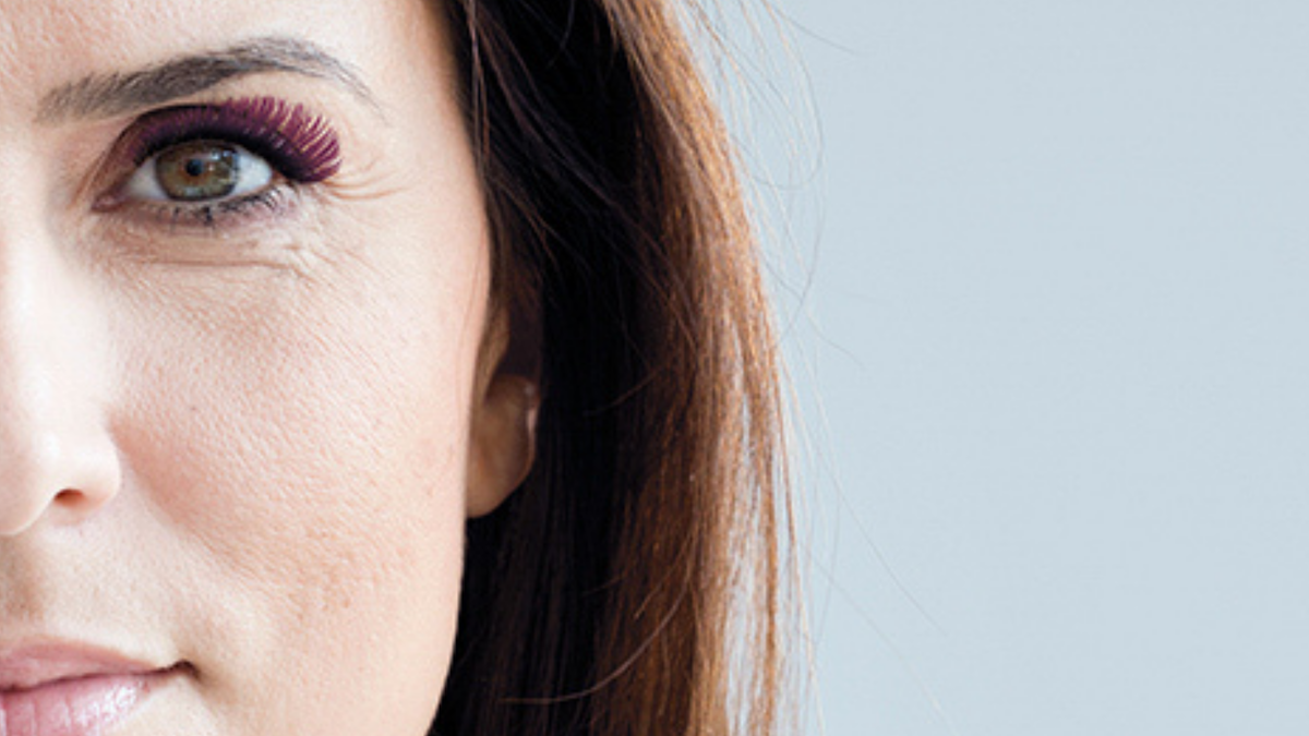 close-up of half of a brunette woman's face featuring pink eyelash extensions on her eye