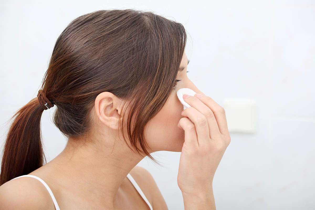 young woman with a ponytail using a round cotton pad to clean her eyelashes