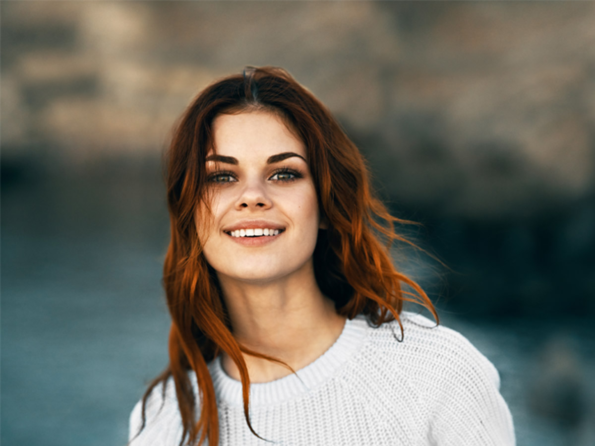 woman with natural lash extensions smiling outside