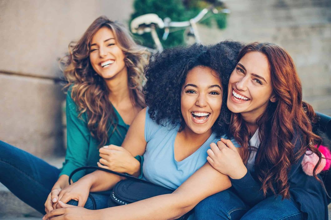 Group of women with eyelash extensions happily hugging