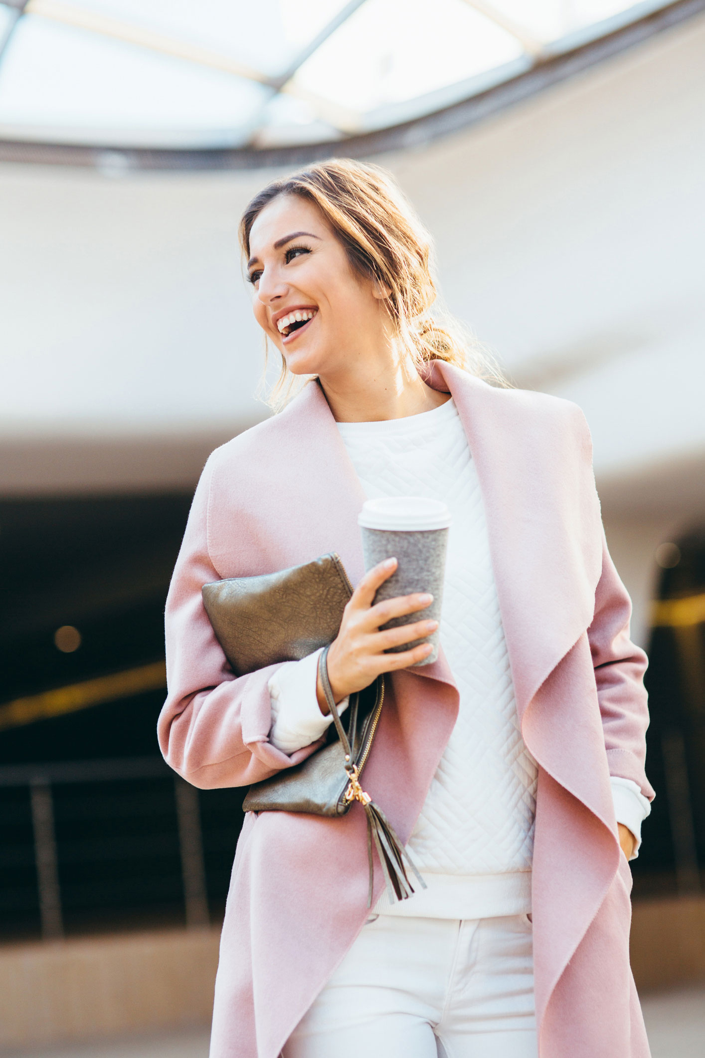 woman in pink cardigan smiling after lash fill