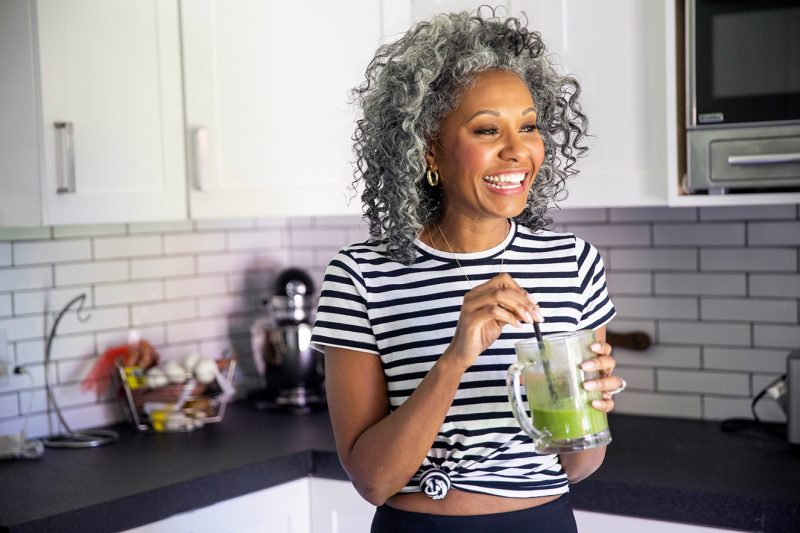 mature black woman with eyelash extensions drinking a smoothie