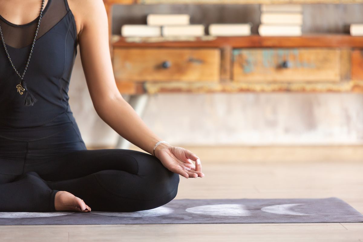 woman in a meditating yoga exercise pose practicing self care