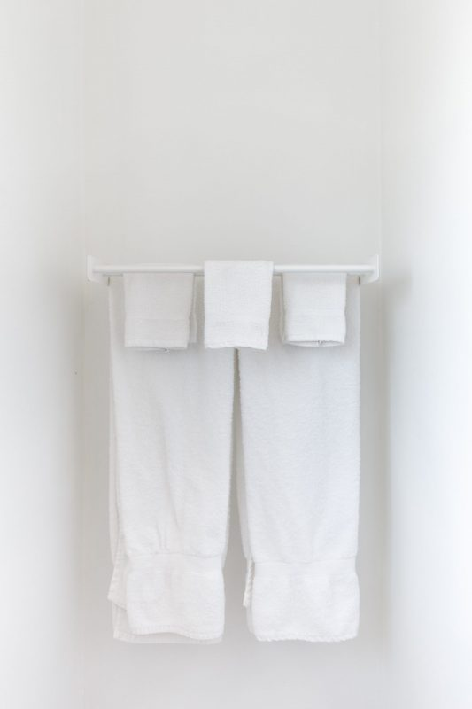 white towel rack with fresh white towels neatly hanging
