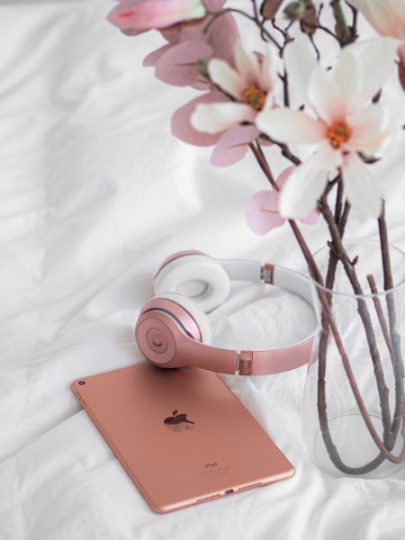 pink headphones and iPad laying on bed with flowers in vase on the right