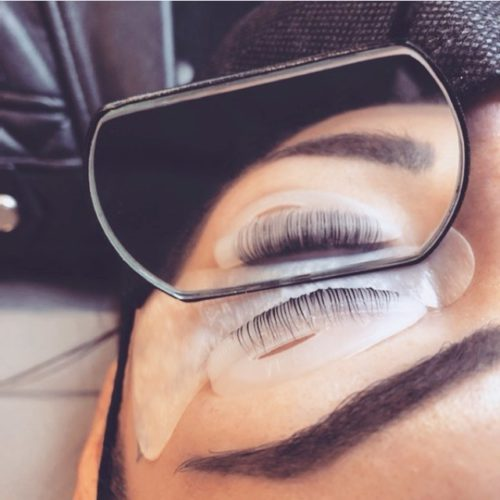 Close-up of a woman's closed eye during a lash lift application