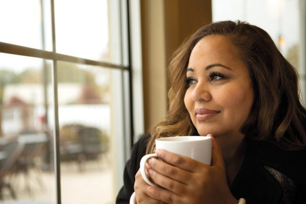 Black woman with lash extensions looking out window with a cup of coffee in her hand