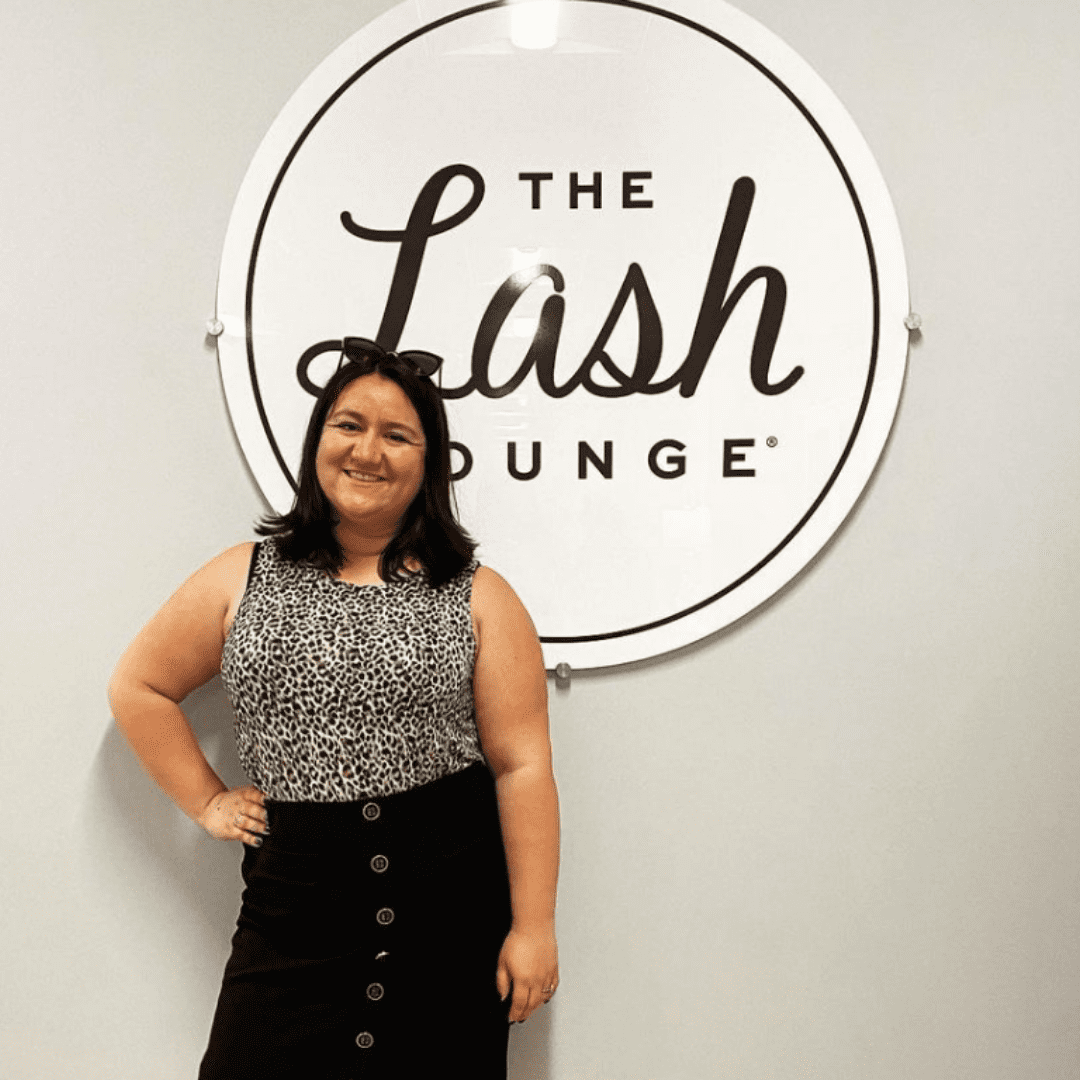Young brunette woman and employee of The Lash Lounge standing in front of the logo