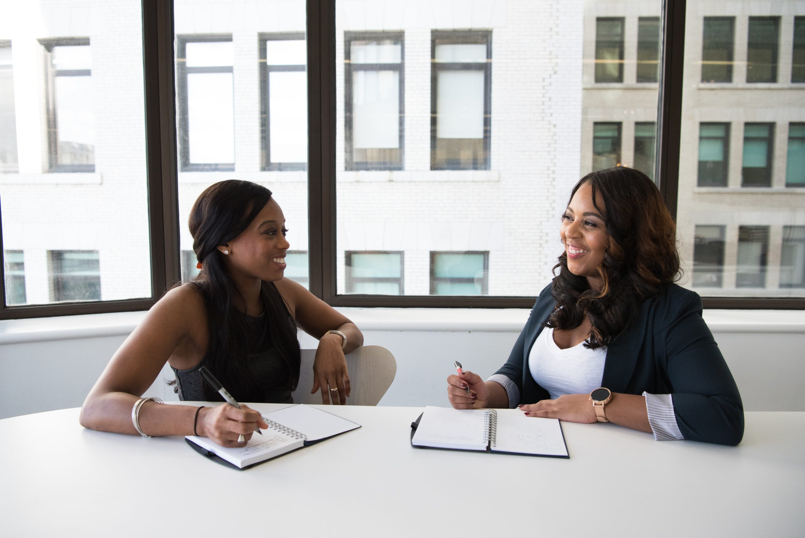 Two black women sitting and smiling in an office setting