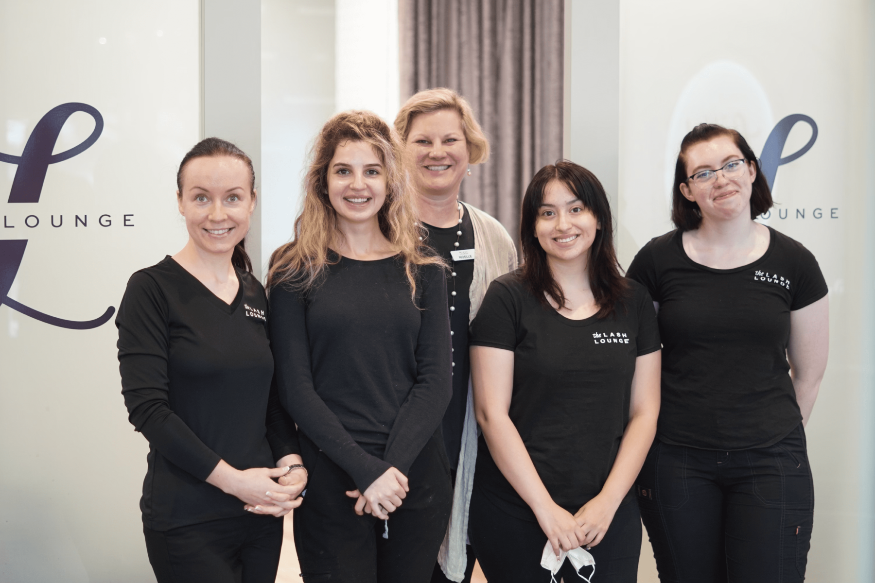 Lash stylists in uniform smiling at The Lash Lounge