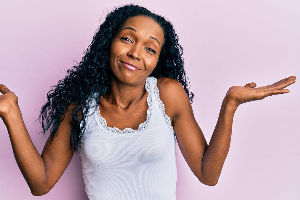 Black girl shrugging shoulders with light purple background